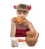 Flickan äter en rulle, och drinkar mjölkar Royaltyfria Foton