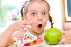 Flickan äter godisar arkivbilder