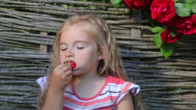 Flickan äter mogna jordgubbar