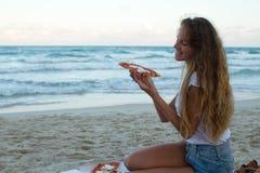 Flickan äter pizza på stranden, en matställe på solnedgången, påklädden för flickan äter fashionably pizza arkivfoton