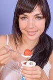 Flickan äter yoghurt arkivbilder