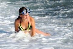Flickan 12 år som spelar i det annalkande havet, vinkar Royaltyfri Fotografi