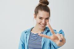 Flickan önskar lycka och fred Charma den bekymmerslösa lyckliga unga le kameran för hand för tecken för kvinnavisningseger fördju fotografering för bildbyråer