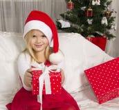 Flickan öppnar en julgåva Royaltyfri Fotografi