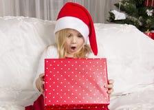 Flickan öppnar en julgåva Royaltyfri Foto