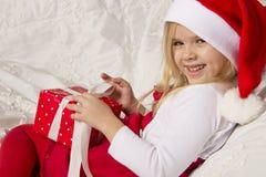 Flickan öppnar en julgåva Arkivbild