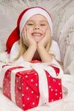 Flickan öppnar en julgåva Royaltyfria Foton