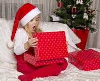 Flickan öppnar en julgåva Arkivbilder