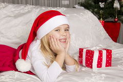 Flickan öppnar en julgåva Arkivfoton