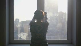 Flickan öppnar fönstren, beundrar stadssikten från fönstret Slowmotion 1920x1080 arkivfilmer