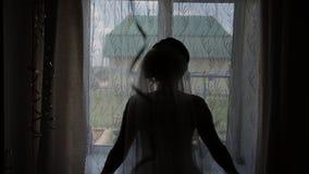 Flickan öppnar gardinerna i morgonen och går ut till terrassen, ultrarapid lager videofilmer