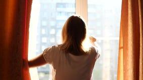 Flickan öppnar gardinerna på en solig dag arkivfilmer