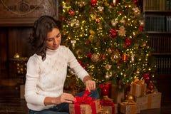 Flickan öppnar julgåvan Royaltyfri Bild