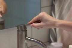 Flickan öppnar metallvattenkranen för tvättande händer arkivfoton