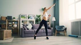 Flickan öva hemma squatting och att lyfta armar som övar i vardagsrum arkivfilmer