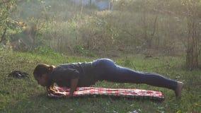 Flickan öva yoga i natur lager videofilmer