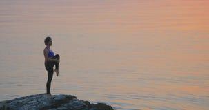 Flickan öva yoga nära havet arkivfilmer