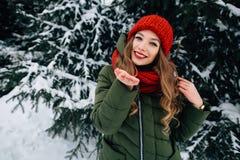 Flickan överför kyssen in camera i snöig vinterdag arkivbilder