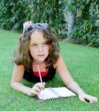 Flickan 12 år skriver i en anteckningsbok Royaltyfri Foto