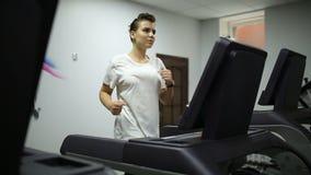 Flickan accelererar på trampkvarnen i idrottshallen lager videofilmer