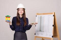 Flickan annonserar mång--våningen byggnad under konstruktion royaltyfri bild