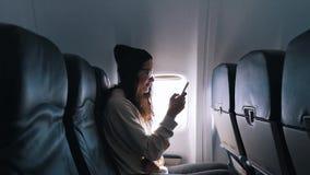 Flickan använder en smartphone under flyget arkivfilmer