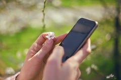 Flickan använder hennes utomhus- mobiltelefon, nära övre solig dag just rained Härlig fruktträdgård Arkivbilder