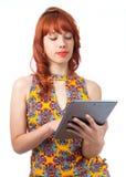 Flickan använder minnestavlan Ung rödhårig mankvinna med sommarklänningen royaltyfria bilder
