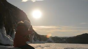 Flickan använder smartphonen på solnedgången stock video