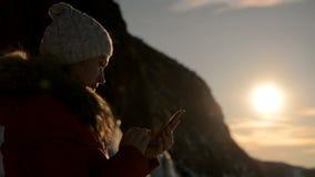Flickan använder smartphonen på solnedgången arkivfilmer
