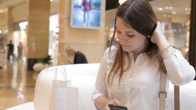 Flickan använder telefonen i gallerian som sitter på en bänk arkivfilmer