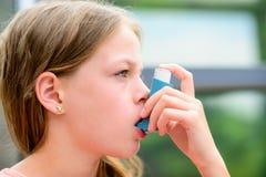Flickan använder en inhalator under en astmaattack Arkivbild