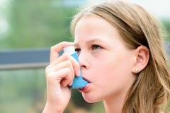 Flickan använder en inhalator under en astmaattack Royaltyfri Fotografi