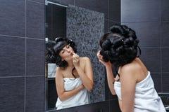 Flickan applicerar läppstift i badrum Royaltyfri Bild