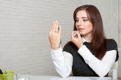 Flickan applicerar läppstift som ser telefonen Fotografering för Bildbyråer