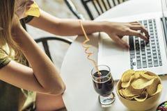 Flickan arbetar p? en dator och ?ter snabbmat royaltyfria bilder
