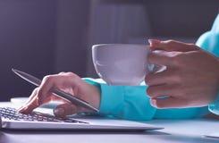Flickan arbetar sent i det mörka kontoret med bärbara datorn Ung affärskvinnaflicka i regeringsställning Närbildfoto av a arkivfoto