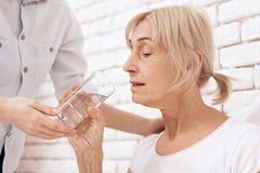 Flickan att bry sig för äldre kvinna hemma Flickan hjälper kvinnan med exponeringsglas av vatten arkivbild
