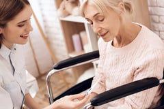 Flickan att bry sig för äldre kvinna hemma Flickan kontrollerar temperatur fotografering för bildbyråer