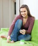 Flickan att bry sig för toenails med spikar lacquer arkivbilder