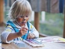 Flickan av 3 år attraktionmålarfärger Fotografering för Bildbyråer