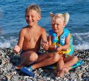 Flickan av 3 år, blondinen och hennes äldre broder på ett hav Royaltyfria Foton
