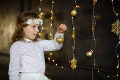 Flickan av 8-9 år med fröjd beundrar guld- julgrangarneringar arkivfoton