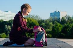 flickan av de höga grupperna, tar ut läroböcker från en rosa ryggsäck i den öppna luften arkivfoto