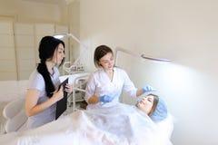 Flickan av den permanenta tatueringkonstnären visar till H för den kvinnliga studenten Royaltyfri Bild