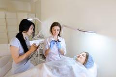 Flickan av den permanenta tatueringkonstnären visar till H för den kvinnliga studenten Royaltyfri Fotografi