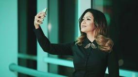 Flickan av det brasilianska utseendet, gör selfie på telefonen arkivfilmer