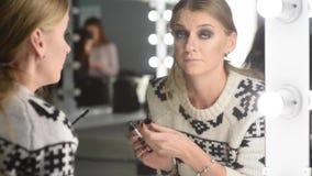 Flickan av spegeln gör framme smink stock video