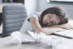 Flickan avverkar sovande att sitta på en grå fåtölj på tabellen, som ligger på hennes notepad och skrynkliga ark av papper Royaltyfri Bild