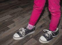 Flickan bär ett par av större skor royaltyfria bilder